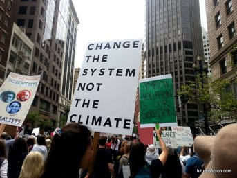 """change the system not the climate"" protest sign"