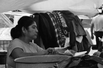 Una profesora reparte comida en el centro de acopio que se ha instalado provisionalmente en el campamento de Revolución. Fotografía: Martina Oliveiro