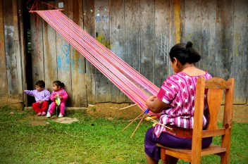 Trabajando sentada el telar de cintura, aprovechando el buen tiempo, las mujeres traman sus hilos afuera de sus casas, decorando los poblados con sus colores. En el Municipio de Pantelhó.