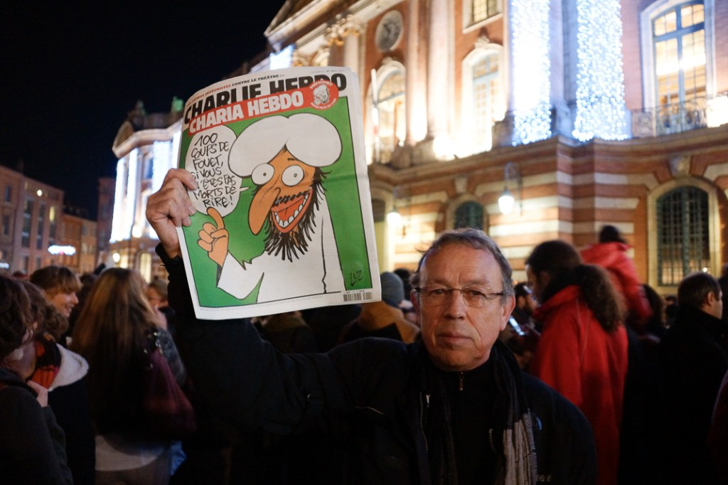 """Un manifestante sostiene el n°1011 del semanario, satíricamente rebautizado """"Charia Hebdo"""""""