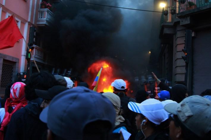 Hoguera frente al contingente de policías que reprimieron el 13 de agosto, en la plaza Santo Domingo del Centro Histórico.