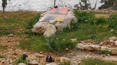 La piedra memorial de Bassem, que murió del impacto de una granada de gas lacrimógeno en su pecho en 2009. Las granadas en el suelo son evidencias de la barbarie que cae sobre Bil'in cada viernes. Fotografía: Susana Norman
