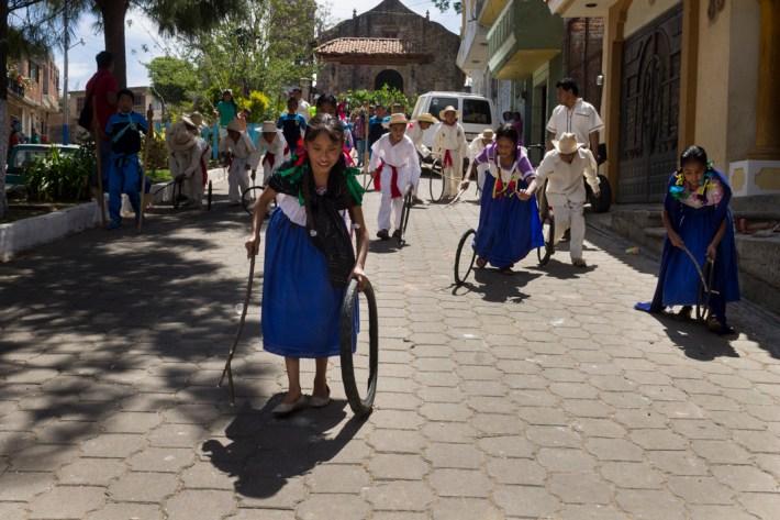 En cada aniversario se hace una gran desfile alrededor del pueblo, en la que participan personas de la comunidad de todas las edades. En esta imagen, niñas y niños representan el juego tradicional del aro. Por Regina López.