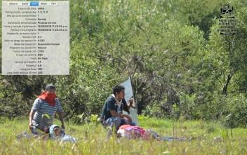 [Foto 9] 11:25:23 am. Yalid Jiménez, yace en el suelo sin poder levantarse, las dos personas que tratan de auxiliarlos están hincadas ya que en ese momento continuaba la policía disparando hacia ese lugar.