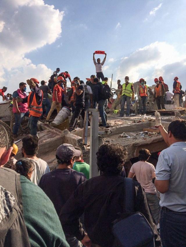 Con cartulinas, rescatistas piden guardar silencio para poder escuchar a las personas atrapadas entre los escombros en Zapata y Prolongación Petén, colonia Emperadores. Fotografía: Agencia Subversiones, licencia copyfarleft P2P.