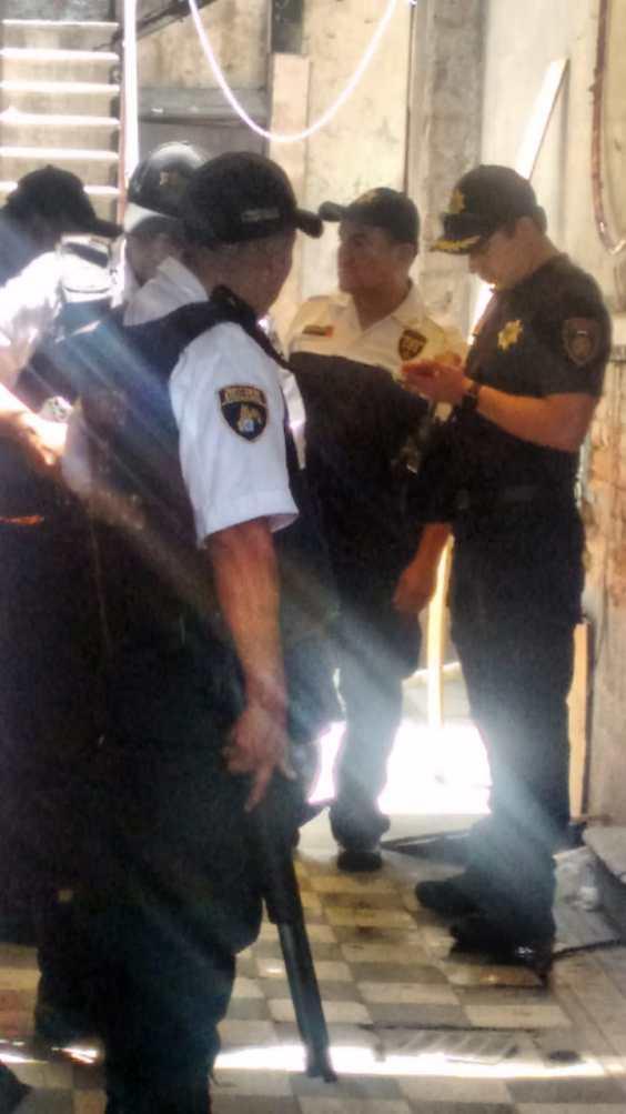 Elementos del CUSAEM custodian con armas largas los departamentos desalojados.