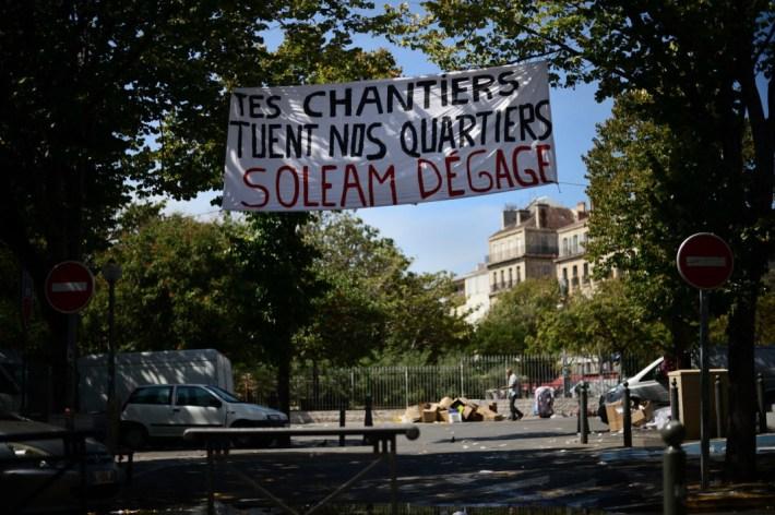8 spt. 2018. Después del mercado en La Plana las mantas dicen: «Tus obras matan nuestros barrios. Fuera SOLEAM»