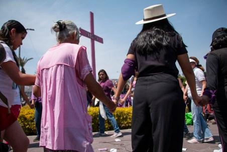 """Mujeres que acompañan la marcha del 8 de marzo en Neza se toman de las manos y hacen un círculo a lado de las cruces rosas que se ubican frente a Palacio Municipal. Este momento de abrazo colectivo forma parte del performance de la colectiva """"Invisibles somos visibles"""" de Ecatepec, Estado de México."""
