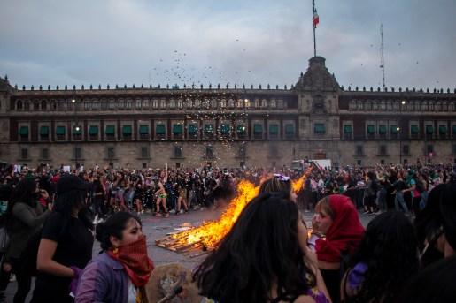 Mujeres bailan alrededor de la fogata frente a Palacio Nacional. Ellas brincan, corren y se abrazan en un aquelarre feminista mientras gritan «El que no brinque es macho, el que no brinque es macho». Al fondo una mujer dispara papelitos de colores que se suman al fuego.