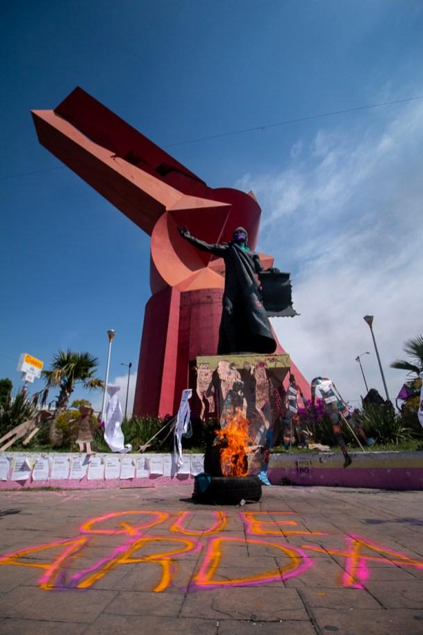 """El 8 de marzo nos encontramos en el Coyote Rojo con madres y familiares víctimas de feminicidio y desaparición forzada de Neza y Chimalhuacán, y colectivas feministas. Antes de comenzar la marcha hacia Palacio Municipal, mujeres pintaron """"Que arda"""" en el piso de la glorieta y prendieron fuego frente a la escultura de Nezahualcóyotl."""