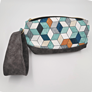Teals, grays, and browns geometic pattern on exterior top of bag and gray vinul for bottom and strap