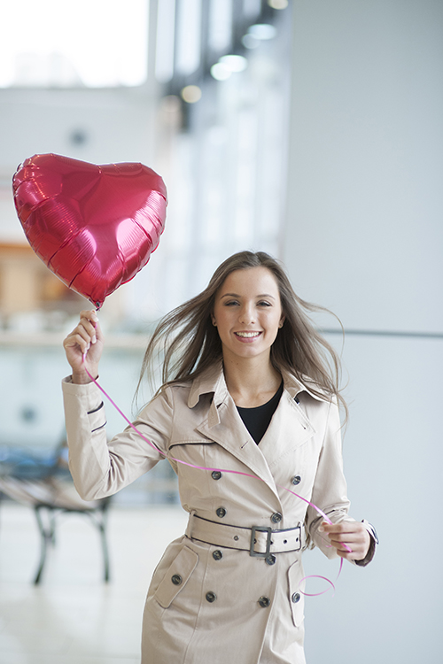Businesswoman holding heart shaped balloon and smiling