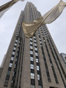 Rockefeller center with flag blowing in the wind.