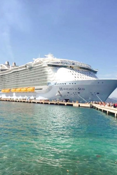 The cruise ship docked at port overlooking crystal clear water.