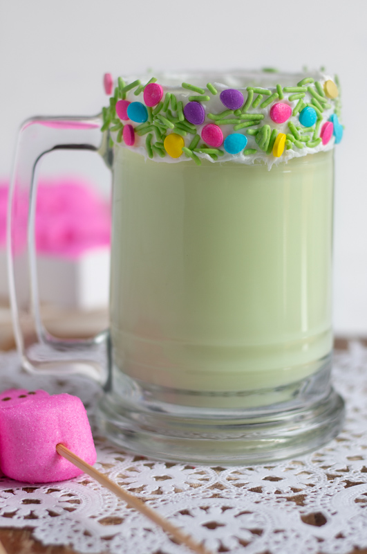 Green milkshake in a glass cup with a sprinkle-frosted rim.