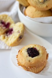 Bowl of Blackberry muffins with blackberry muffin cut in half.