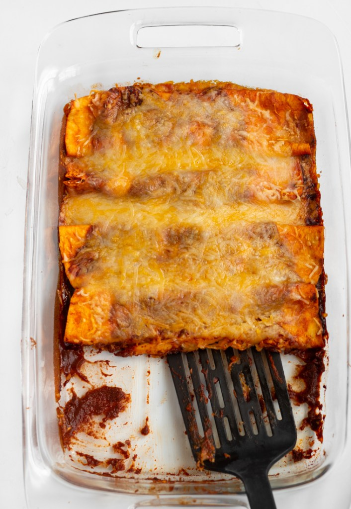 Spatula scooping out enchiladas from casserole dish.