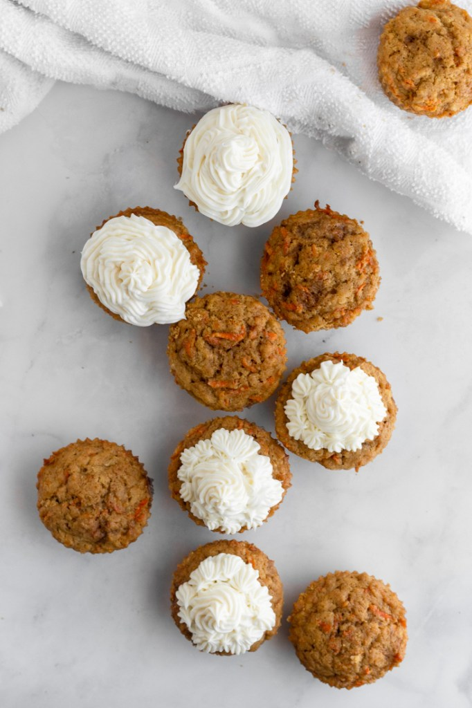 Carrot Cake Cupcakes scattered on marble surface.