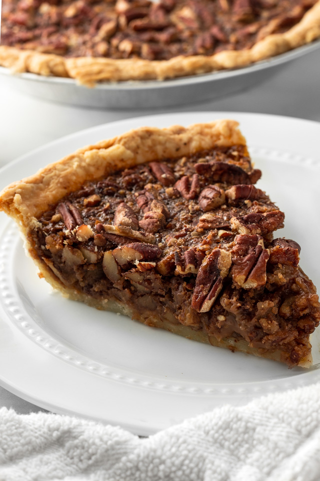 Slice of pecan pie on a white plate with a white napkin.