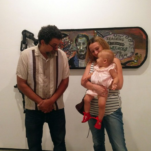 "Anastasia Louise Sudentas at the David B. Frye's exhibition, in front of the painting ""Teaching monetized Negroes to pray"""