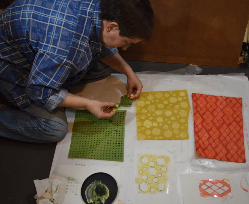 Sue Clancy in the process of stenciling patterns on handmade hand dyed papers