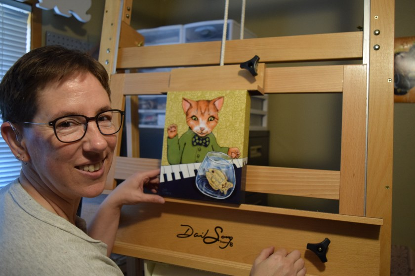 "Sue Clancy putting one of her recent artworks on the new easel ""to see how it'd work""."