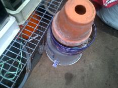 Our Greenhouse Heater.. two clay terracotta pots one inside the other with a candle inside both stood on a tin box.. This heats the Green house slightly to keep out any frost if the night temperature drops