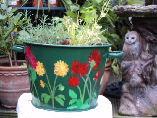 Painted large tub with Dahlia flowers now planted with herbs