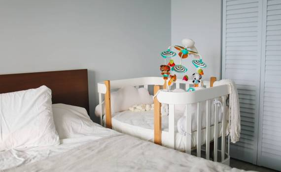 crib next to bed in bedroom