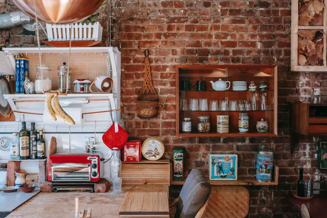 interior of cozy kitchen with many shelves and kitchenware