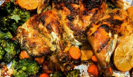 A golden butterflied chicken with roast vegetables in a one-pan meal