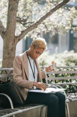 focused young black female manager reading documents and having lunch on bench in park