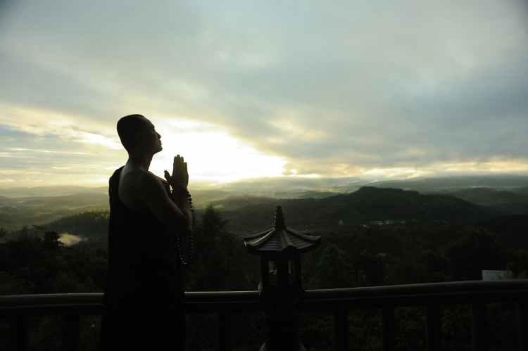 monk holding prayer beads across mountain