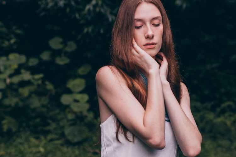 woman closing her eyes wearing white tank top