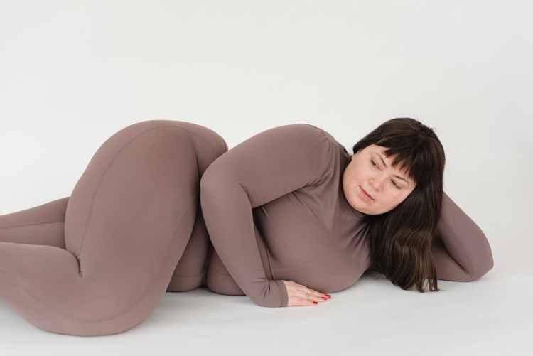 overweight woman gracefully lying on floor in studio