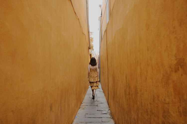 back view of a woman walking in a narrow alley