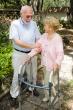 elderly man helping woman on walker