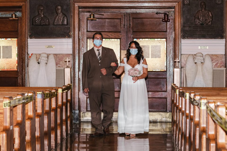 walking-down-the-aisle-with-masks-on-pandemic-covid-19-2020-wedding-at-church