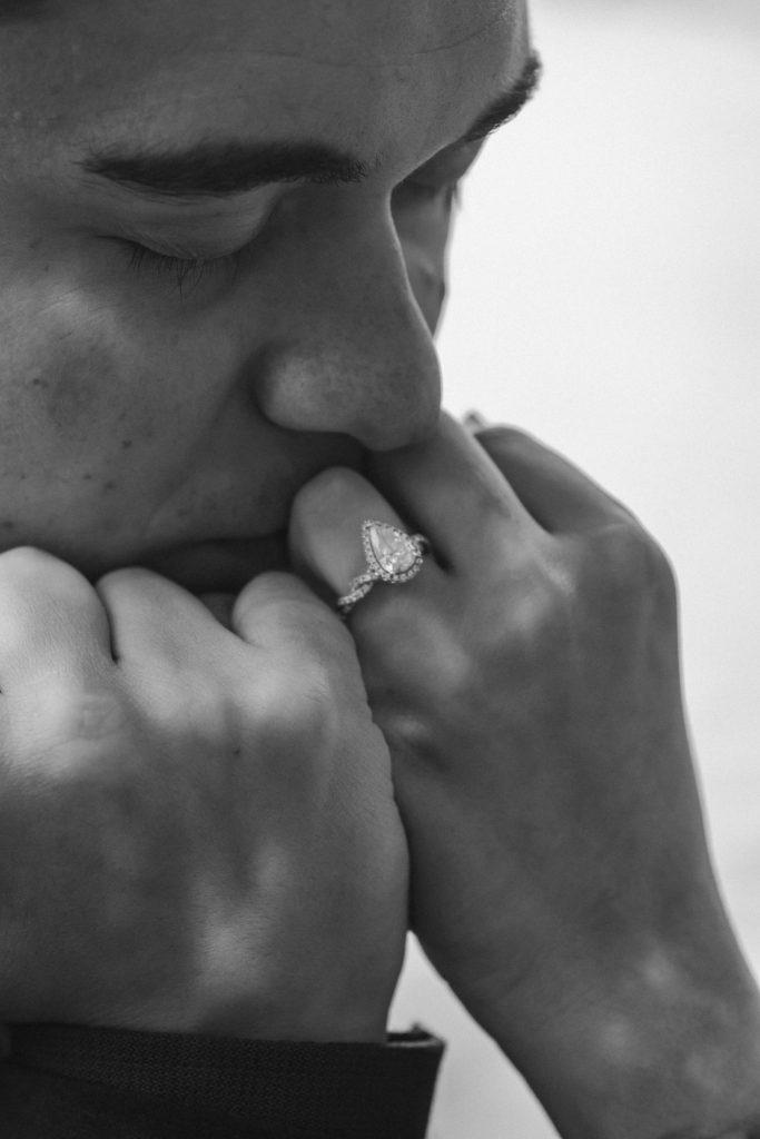 black-and-white-photo-groom-kissing-wedding-ring-suessmoments