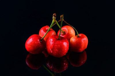 Cherries on black with reflections
