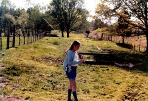 Addie walks through a cow pasture with a fishing pole