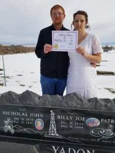 Inexplicably, Aaron Stout and his new bride, Mckenley, holding their marriage certificate over the grave of some members of Mckenley's family. I got nothing, folks.