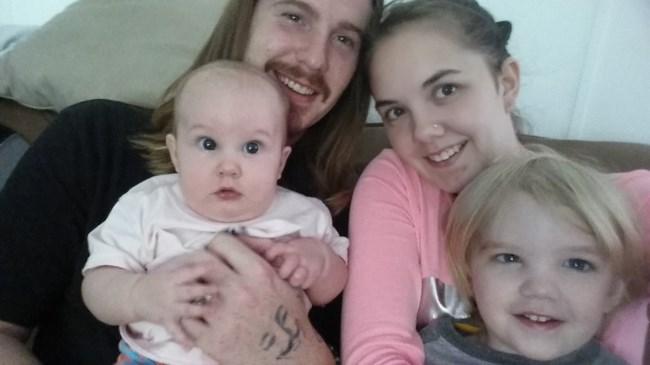 Zachary Littell holding daughter Ava and Abigail Neiger-Bickham holding son Jaxson