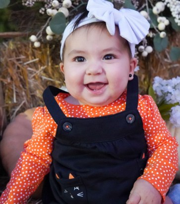 Baby Marion Jester-Montoya in her Halloween outfit with a bow on her head