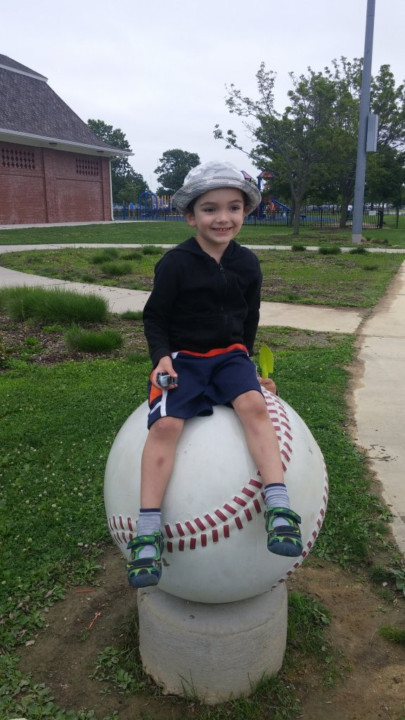 Thomas Valva sitting on a giant baseball