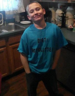 """James Alexander Hurley wearing a blue t-shirt reading """"Dirt: Boy Glitter"""""""