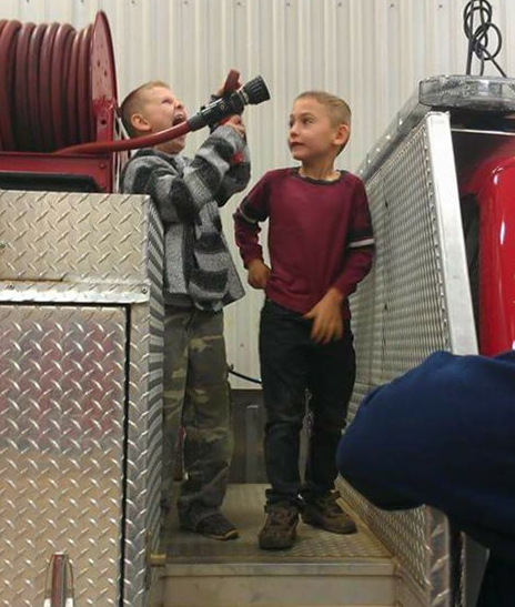 Austin Cameron and brother James Alexander Hurley on a firetruck
