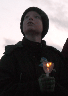 A child attends a vigil for murdered Montana 12-year-old James Alex Hurley.