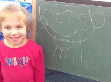 Raylee Browning next to a drawing she made on a chalkboard