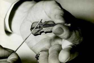 Hand playing tiny violin
